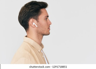 Side view portrait of serious young handsome man posing with wireless earphones on white studio background. Caucasian businessman using wireless headphone.