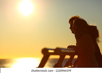 Side view portrait of a silhouette of a couple looking at horizon at sunset