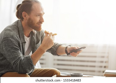 Side view portrait of smiling bearded man watching TV at home and eating pizza during lazy weekend, copy space