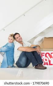 Side view portrait of a smiling couple with boxes in a new house