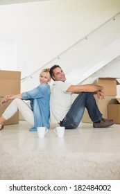 Side view portrait of a smiling couple with cups and boxes in a new house