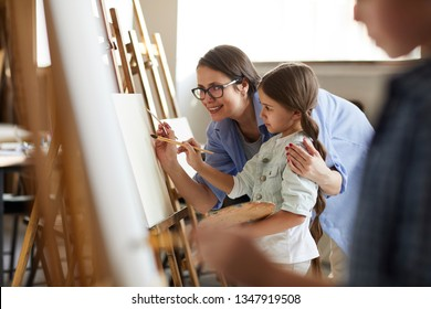 Side view portrait of smiling female teacher helping little girl painting picture on easel in art class, copy space
