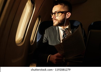 Side view portrait of smiling young businessman looking in window enjoying sunset view from plane, copy space