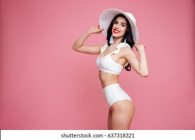 Side view portrait of a stylish pretty woman wearing swimsuit and summer hat and looking at camera isolated over pink background