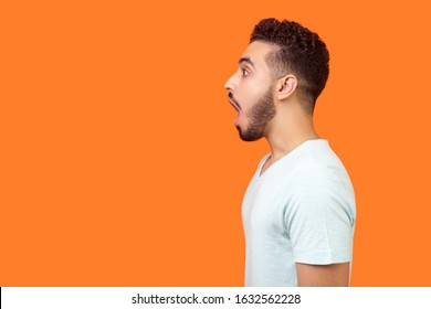 Side view portrait of surprised brunette man with beard in white t-shirt looking left with big eyes and open mouth, shocked by news, empty copy space for text. studio shot isolated, orange background