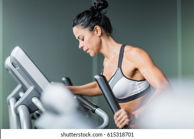 Side view  portrait of sweaty fit woman exercising using elliptical machine  during intense workout in modern gym