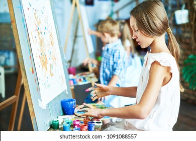 Side view portrait of talented teenage girl painting beautiful picture on easel in art class, working with other children