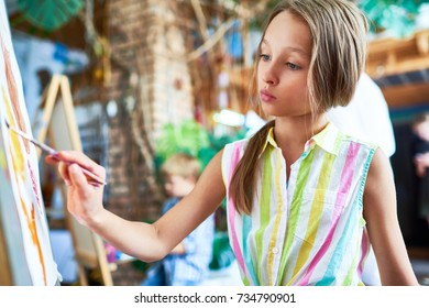Side view portrait of talented teenage girl painting beautiful picture on easel in art class, with other children  in background