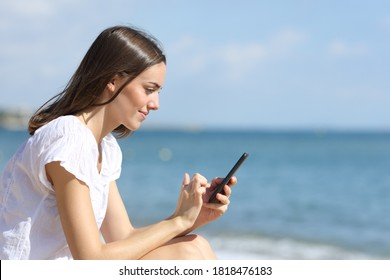 Side view portrait of a teen using smart phone sitting on the beach