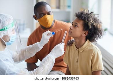 Seitenbild des jungen afroamerikanischen Jungen, der in der Klinik einen Covid-Test mit männlichen Krankenschwestern mit Tube und Glasrohr-Halsband-Tube-und Schwabenhalm