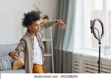 Side view portrait of teenage African-American boy filming videos at home and dancing to camera set on ring light, young blogger concept, copy space