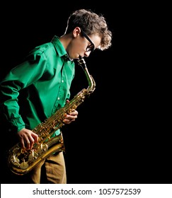 Side view portrait of a teenage boy playing the saxophone