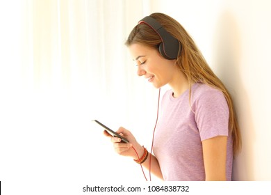 Side view portrait of a teenager listening to music on line using a phone