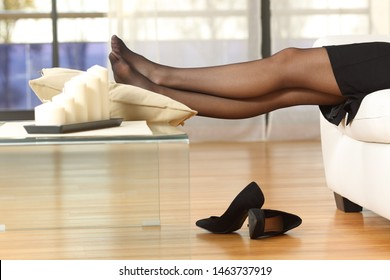 Side view portrait of a tired businesswoman resting after work sitting on a couch at home