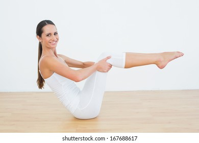 Side view portrait of a toned young woman doing the boat pose in fitness studio