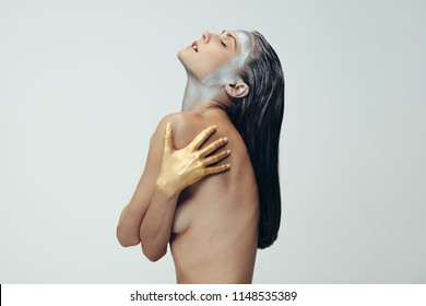 side view portrait of topless woman posing against grey background with body paint. Female model with silver body paint on face and hands colored with gold.