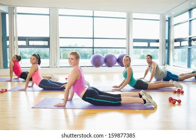 Side view portrait of trainer with class doing the cobra pose in bright fitness studio