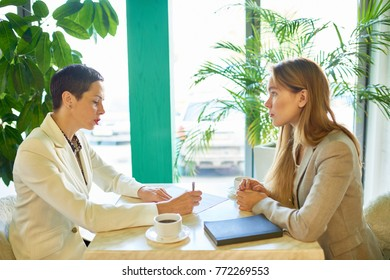 Side view portrait of two modern young women discussing work sitting at table in cafe during business meeting or job interview