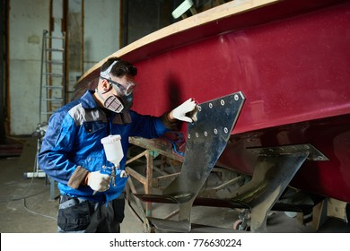 Side view portrait of unrecognizable worker wearing protective mask painting boat in yacht workshop, copy space