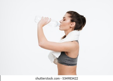 Side view portrait from waist up of young sports woman drinking water from a bottle with towel around her neck isolated on a white background