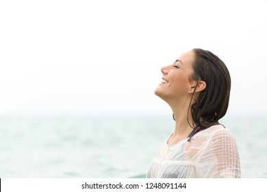 Side view portrait of a wet clothed woman breathing fresh air on the beach