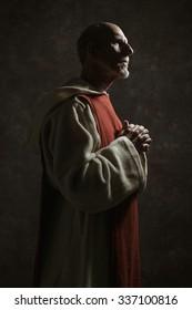 Side view portrait of wishing monastic. Studio shot against dark wall.