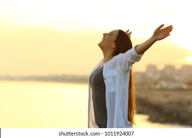 Side view portrait of a woman breathing deep fresh air outstretching arms at sunset with the city in the background