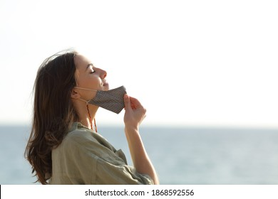 Side view portrait of a woman breathing deep fresh air relieving taking off mask due covid on the beach