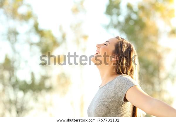 Seitenbild einer Frau, die im Sommer frische Luft im Freien mit Bäumen und Himmel im Hintergrund atmet