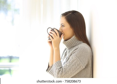Side view portrait of a woman drinking coffee looking through a window in a house interior