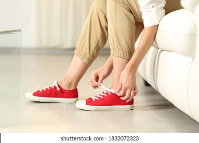 Side view portrait of a woman hands tying shoelaces of sneakers at home