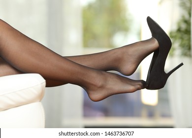 Side view portrait of a woman legs with stockings taking off shoes on a couch at home