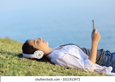 Side view portrait of a woman relaxing listening to music lying on the grass with the sea in the background