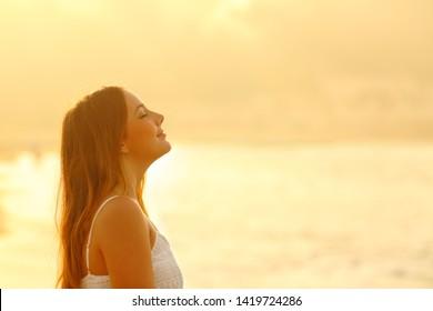 夕焼けの時、海岸で新鮮な空気を深く吸いながらくつろいでいる女性の側面図