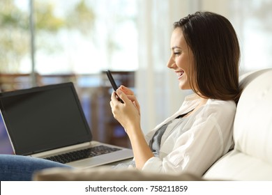 Side view portrait of a woman using a smart phone and a laptop sitting on a sofa in the living room at home