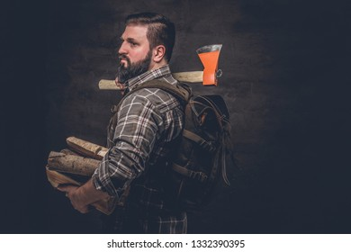 Side view portrait of a woodcutter with a backpack dressed in a plaid shirt holding firewood and ax. Studio photo against a dark textured wall