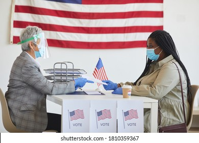 Side view portrait of young African-American woman wearing mask while registering for voting on post-pandemic election day, copy space