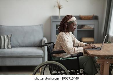 Seitenbild der jungen afroamerikanischen Frau, die Rollstuhl benutzt, während sie von zu Hause aus in minimalgrauem Innenraum arbeitet, Kopienraum