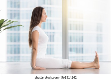 Side view portrait of young attractive woman practicing yoga, sitting in Dandasana exercise, Staff pose, working out, wearing white sportswear, indoor full length, near floor window with city view