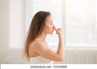 Side view portrait of young attractive yogi woman practicing yoga, making Alternate Nostril Breathing exercise, working out using nadi shodhana pranayama, white color room background, eyes closed