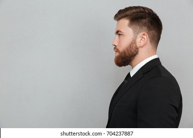 Side view portrait of a young bearded man in suit looking forward isolated over gray background