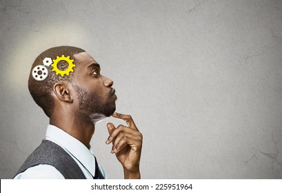 Side view portrait young business man thinking deciding finger on chin looking up gear mechanism over head isolated grey wall background copy space. Emotion facial expression perception intelligence