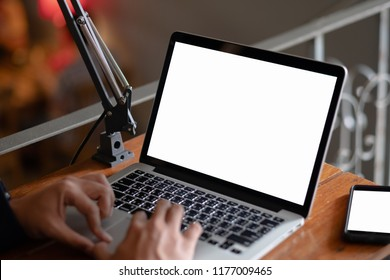 Side view portrait of young businessman having business call in office, her workplace, writing down some information. Man talking on mobile phone, asking questions, looking at pc screen.