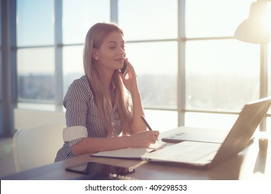 Side view portrait of young businesswoman having business call in office, her workplace, writing down some information. Woman talking on mobile phone, asking questions, looking at pc screen.