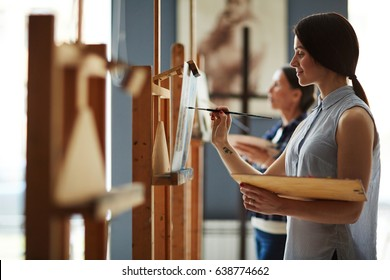 Side view portrait of young female student in art class, enjoying painting oil picture on canvas