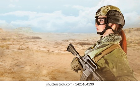 Side view portrait of young fully equipped military soldier woman holding an automatic rifle M16 on desert background.
