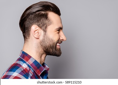 A side view portrait of young handsome smiling man with stylish haircut standing against gray background.