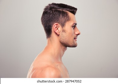 Side view portrait of a young man with nude torso over gray background