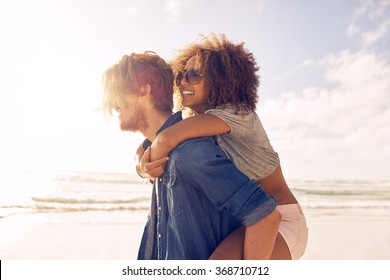 Side view portrait of young man carrying his girlfriend on his back at the beach. Boyfriends giving piggyback ride to his beautiful girlfriend at seashore.