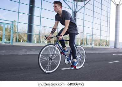 Side view portrait of a young man riding on bicycle in city street. Man on blue bicycle with white wheels, big mirror windows background